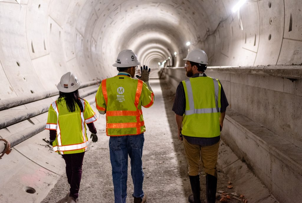 Walking Through The Half-Mile-Long Tunnel That Will Connect Metro Rail's Future Little Tokyo/Arts District Station To Its Future Historic Broadway Station, Regional Connector Director Of Construction Management Rajni Patel (Center) Explains The Project To Corsair Staff Writer Michael Fanelli (Right). They Are Accompanied By Regional Connector Senior Safety Manager Michelle Jones (Left) As They Walk Underneath 2nd Street In Downtown Los Angeles On Wednesday, April 3, 2019. When Completed In 2022, The Regional Connector Will Simplify East-West And North-South Transportation In Los Angeles. For Example, To Travel From East Los Angeles College To Santa Monica College Currently Takes 3 Trains, But Will Only Require One Train In 2022. (Glenn Zucman/The Corsair)