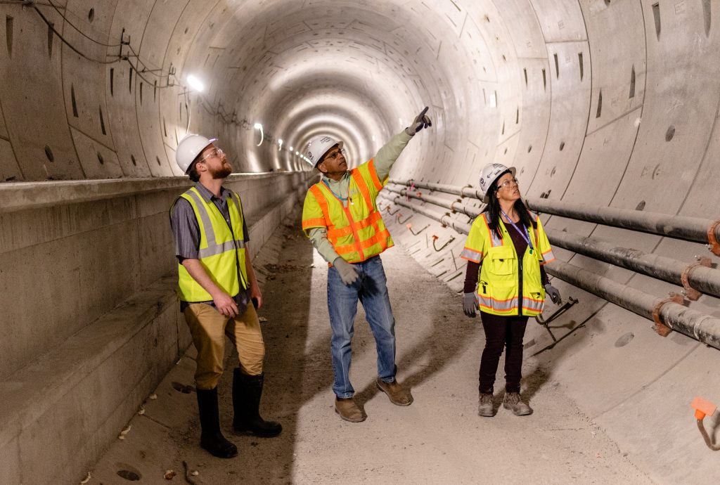 Walking Through The Half-Mile-Long Tunnel That Will Connect Metro Rail's Future Little Tokyo/Arts District Station To Its Future Historic Broadway Station, Regional Connector Director Of Construction Management Rajni Patel (Center) Explains The Project To Corsair Staff Writer Michael Fanelli (Left). They Are Accompanied By Regional Connector Senior Safety Manager Michelle Jones (Right) As They Walk Underneath 2nd Street In Downtown Los Angeles On Wednesday, April 3, 2019. When Completed In 2022, The Regional Connector Will Simplify East-West And North-South Transportation In Los Angeles. For Example, To Travel From East Los Angeles College To Santa Monica College Currently Takes 3 Trains, But Will Only Require One Train In 2022. (Glenn Zucman/The Corsair)