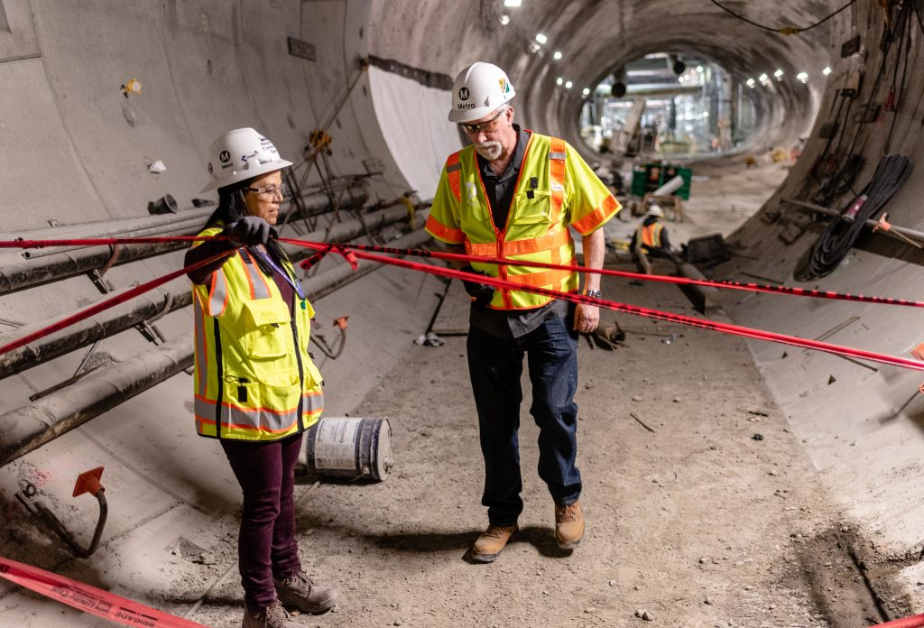 Metro Regional Connector Senior Safety Manager Michelle Jones Lifts Construction Tape For Metro Media Relations Communications Manager Rick Jager As They Walk Through The Half-Mile-Long Tunnel Beneath 2nd Street In Downtown Los Angeles On Wednesday, April 3, 2019. When Completed In 2022 The Regional Connector Will Add New Stations At Little Tokyo/Arts District, Historic Broadway, And Grand Avenue Arts/Bunker Hill. The Regional Connector Will Simplify East-West And North-South Travel In Los Angeles. A Trip From East Los Angeles College To Santa Monica College Which Currently Requires 2 Transfers And 3 Trains, Will Require Only One Train When This New Segment Opens In 2022. (Glenn Zucman/The Corsair)