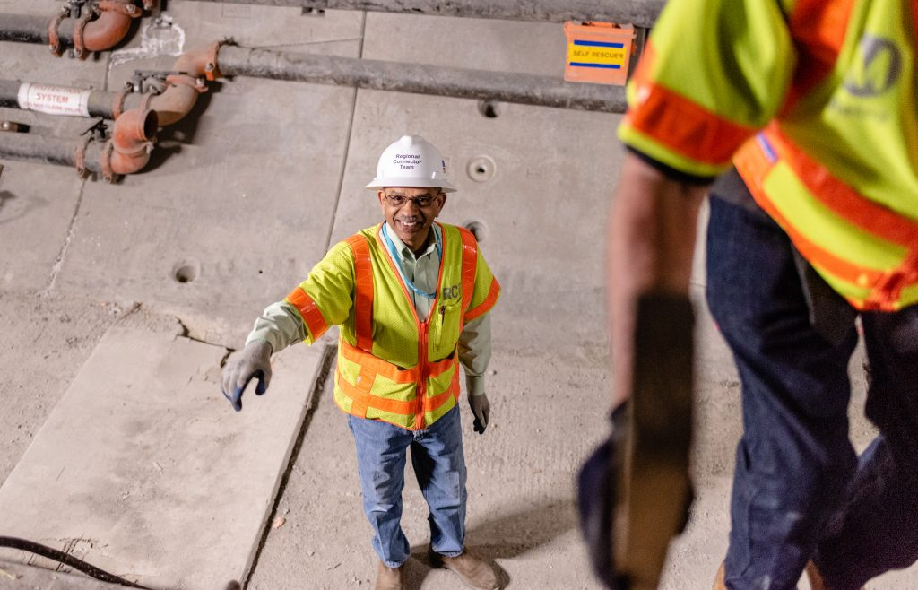 Metro Regional Connector Director Of Construction Management Rajni Patel Smiles As He Prepares To Follow Media Relations Communications Manager Rick Jager Up A Temporary Wooden Ladder That Connects The Two Metro Rail Tunnels Running Beneath 2nd Street In Downtown Los Angeles On Wednesday, April 3, 2019. When Completed In 2022 The Regional Connector Will Add New Stations At Little Tokyo/Arts District, Historic Broadway, And Grand Avenue Arts/Bunker Hill. The Regional Connector Will Simplify East-West And North-South Travel In Los Angeles. A Trip From East Los Angeles College To Santa Monica College Which Currently Requires 2 Transfers And 3 Trains, Will Require Only One Train When This New Segment Opens In 2022. (Glenn Zucman/The Corsair)