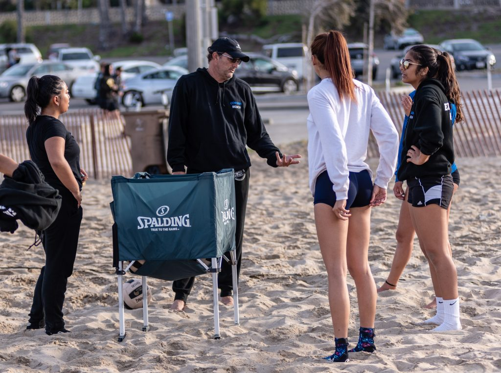 Assistant Coach Tom Slauterbeck Discusses Technique With Players Caitlin Quijano, Angelina Burton And Maria Larranaga At Corsair Beach Volleyball Practice At Santa Monica Beach On Tuesday Morning March 26, 2019. The SMC Corsairs Beach Volleyball Season Began In February And Runs Through April 2019. (Glenn Zucman/The Corsair)
