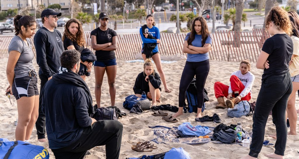 With His Back To The Camera, SMC Beach Volleyball Head Coach Dan Freeman Holds A Brief Team Meeting At The End Of Practice At Santa Monica Beach On Tuesday, March 26, 2019. The Beach Volleyball Season Began In February And Runs Through April 2019. (Glenn Zucman/The Corsair)