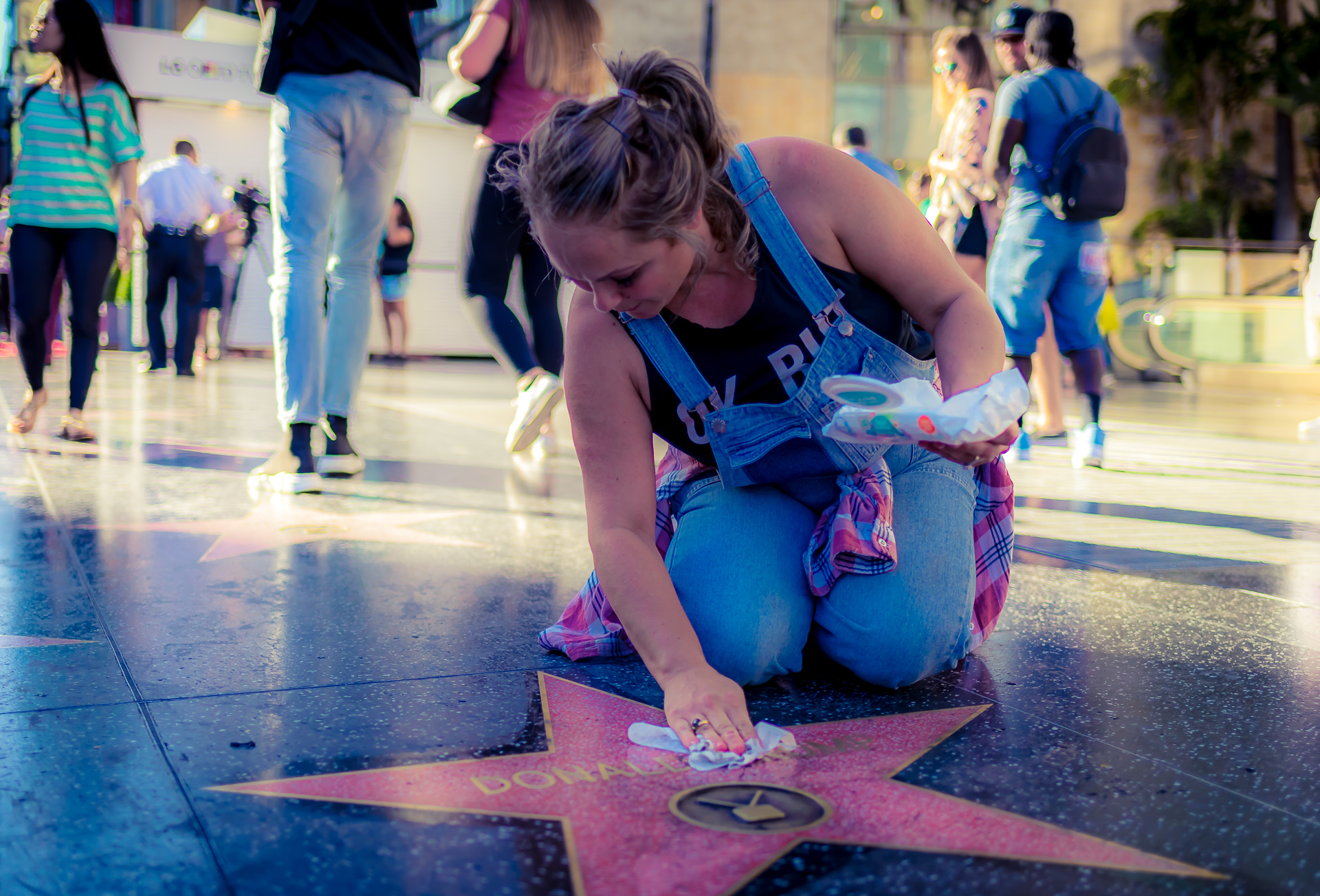 a woman in denim overalls kneeling at Donald Trump's star on Hollywood Blvd and cleaning it with baby wipes