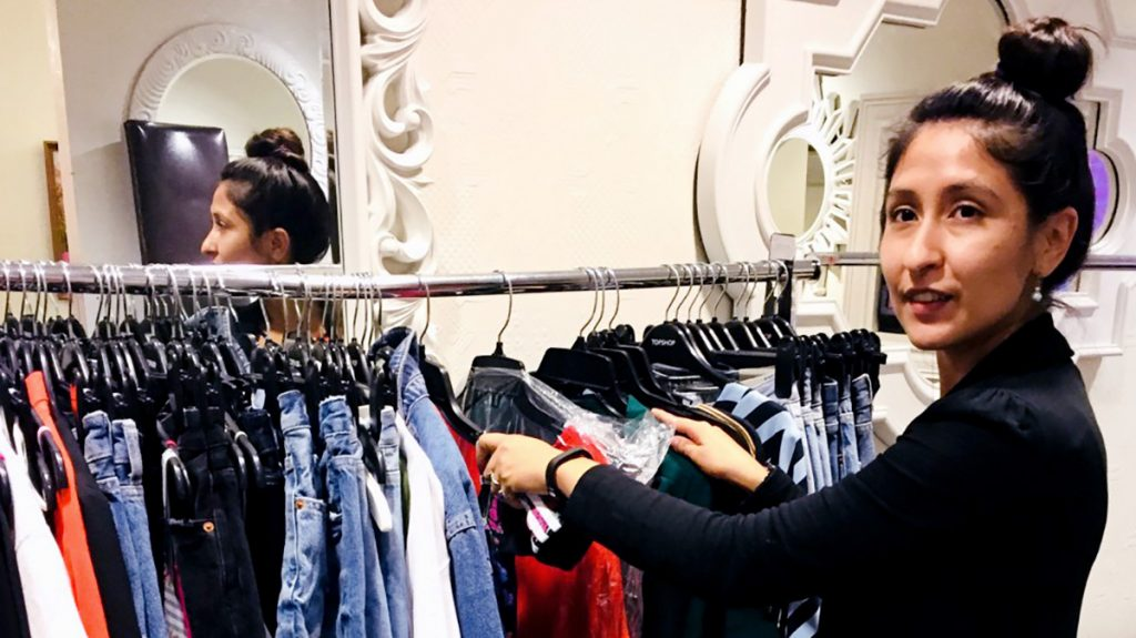 Stephanie Eve Urness working with a rack of clothing